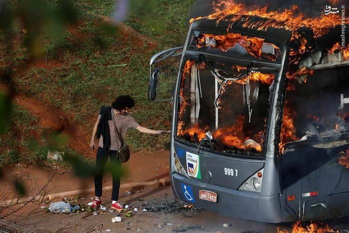 روشنکردن سیگار با اتوبوسی که در آتش اعتراض برزیلیان نسبت به کاهش هزینههای عمومی دولت سوخته است