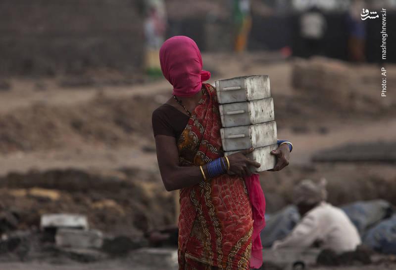 زن هندی در حال کار با قالبهای کوره آجرپزی با صورتِ پوشیدهشده جهت محافظت از گرد و خاک در حیدرآباد