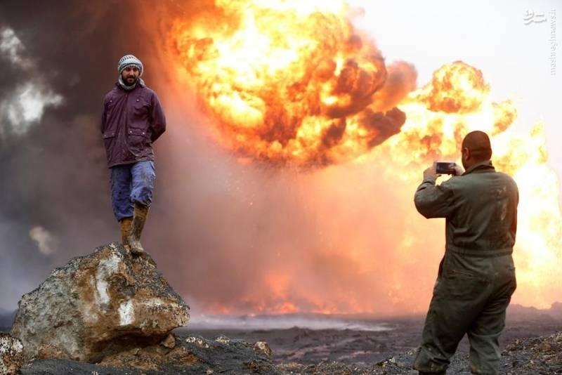 عکس یادگاری با آتشی که نیروهای داعش پیش از ترک القیاره به جان تأسیسات نفتی انداخته است