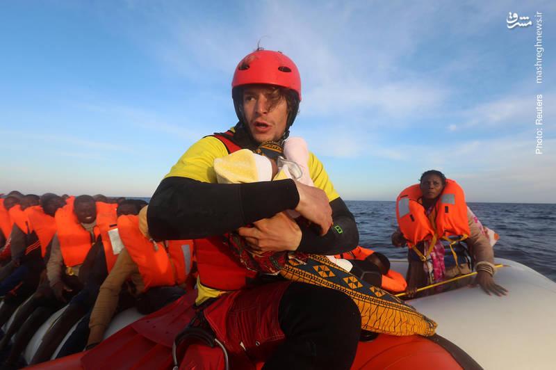 غریقنجاتهای اسپانیایی فعالیت مستمری برای نجات جان مهاجران آفریقایی در دریای مدیترانه دارند. تصویر نشان میدهد دنیِل از یک نوزاد چهارروزه در برابر مرگ مراقبت میکند.