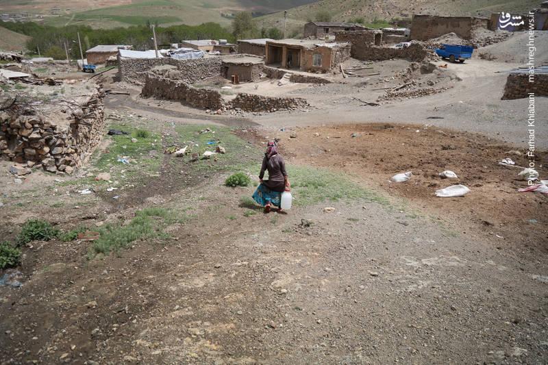 زن جوانی که برای خانه اش از چشمه آب می برد