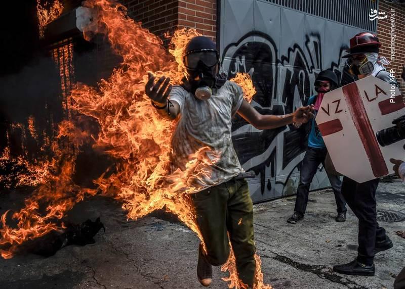 آتشگرفتن تظاهرکنندگان علیه مادورو بواسطه انتشار بنزین از باکِ موتورسیکلتی که خود آتش زده بودند