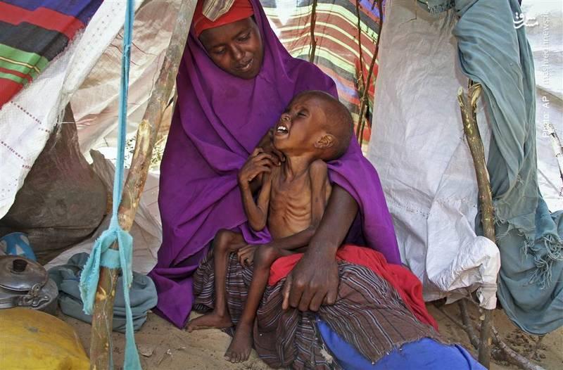 ابراهیم در آغوش مادرش صحرا در اردوگاه موگادیشو. کودکان سومالیایی بر اثر خشکسالی در میانه اقدامات تروریستی گروه الشباب به شدت آسیبپذیر شدهاند