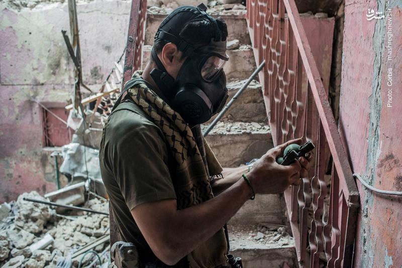 یک نیروی واکنش سریع عراق در موصل، نارنجکها را برای پرتاب بر سر داعشیها آماده میکند