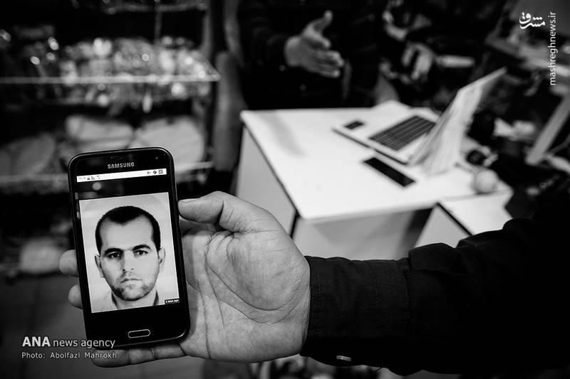 یکی از شهروندان عکس قاتل را به عکاس نشان می دهد.
