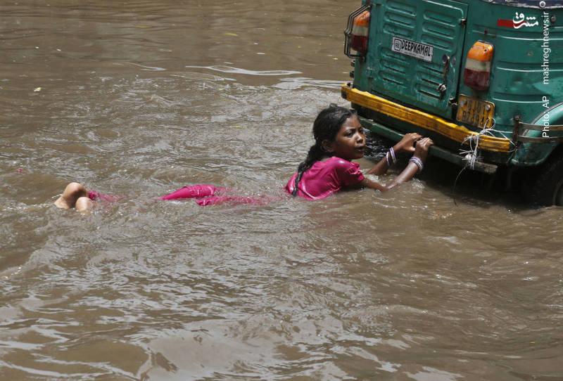 شنای تفریحی پشت یک خودرو پس از وقوع سیل در احمدآباد هند