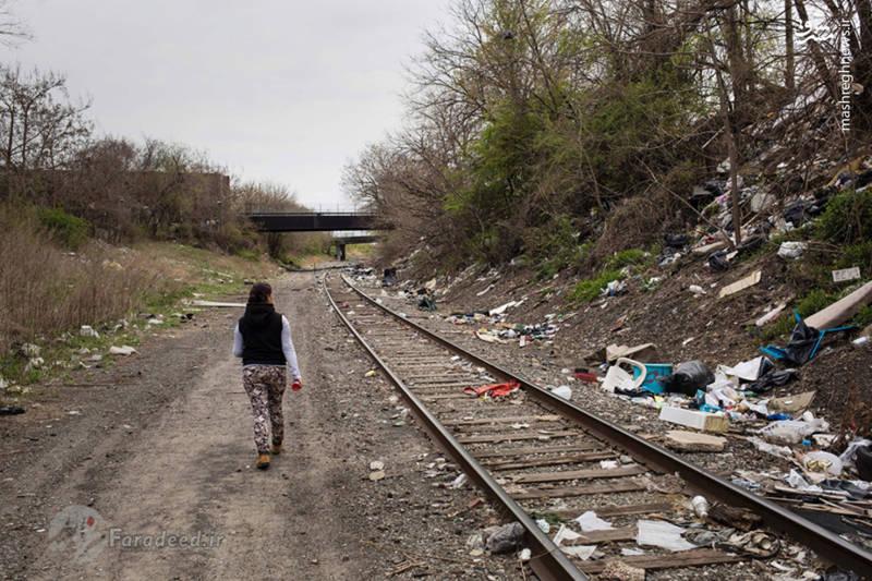 جسیکا یکی از معتادان بی خانمان در حال عبور از کنار خط آهن با انبوهی از زباله های بر جا مانده از استعمال مواد مخدر