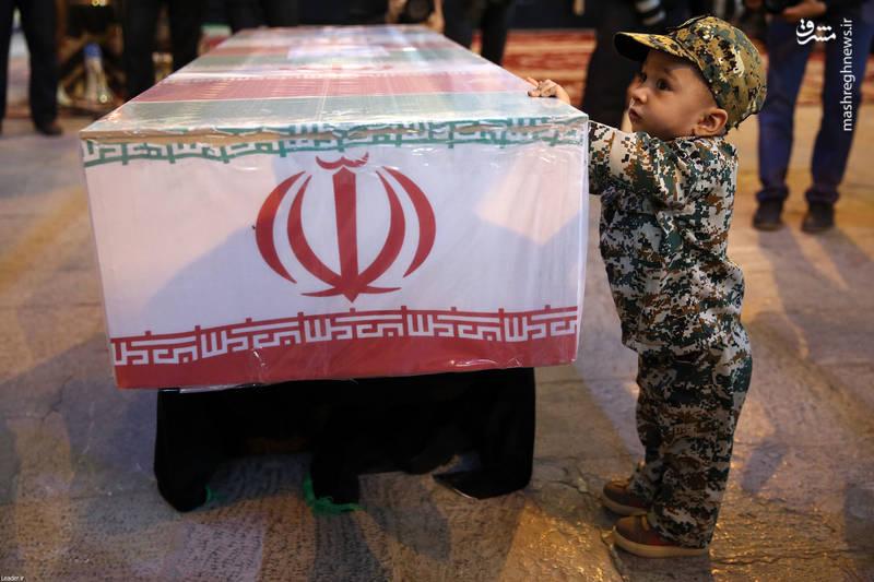 عکس پسر شهید محسن حججی در کنار تابوت پیکر بی سر پدرش