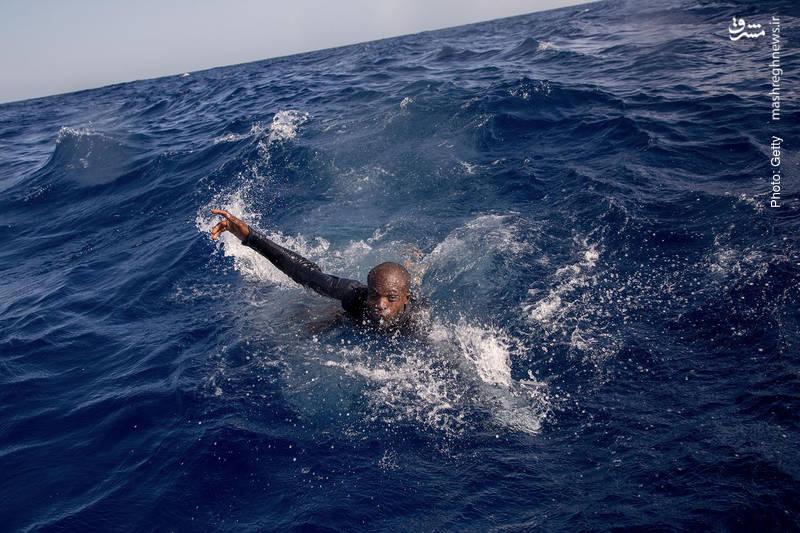 تلاش یک مهاجر در دریای مدتیرانه برای رساندن خود به قایقهای نجات