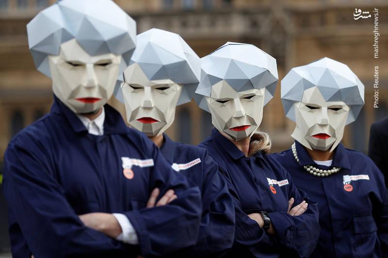 افرادی از سندیکای کارگری GMB در اعتراض به بودجهریزی وزیردارایی فیلیپ هاموند، مقابل پارلمان بریتانیا تجمع کرده و ماسک معروف به «ربات می» را که از چهره نخستوزیر برگرفته شده به سر کردهاند.