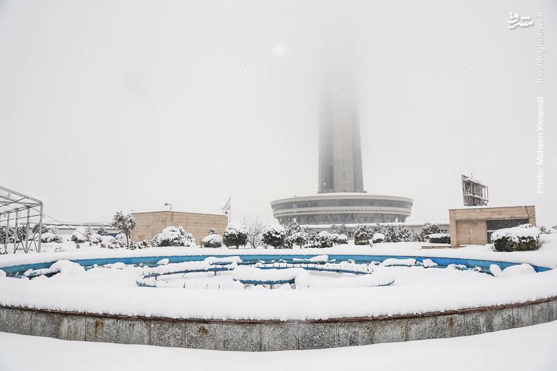 نمایی از برج میلاد، غرق در مه و برف