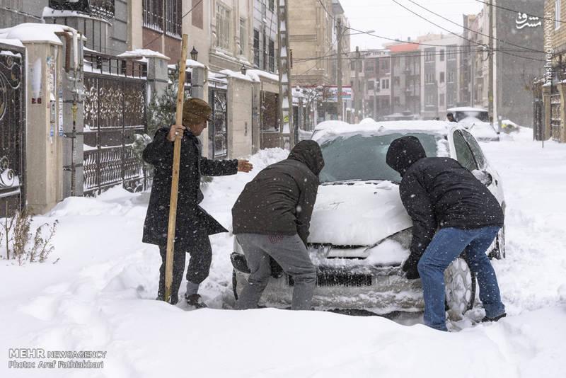 کمک مردم به خودرویی که در برف مانده است.