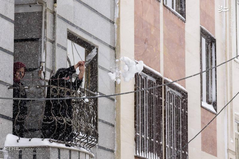 فردی که بالکن خانه خود را برف روبی  میکند.