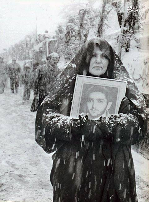 مادر شهید شاهین باقری نیا به همراه عکس فرزندش در هوای برفی