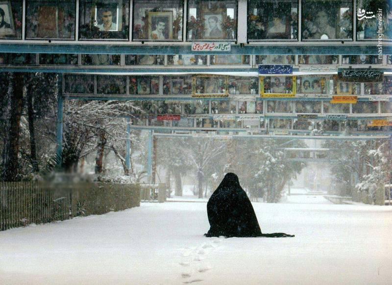 مادر شهیدی که در برف شهید برسر مزار پسرش حضور یافته است.