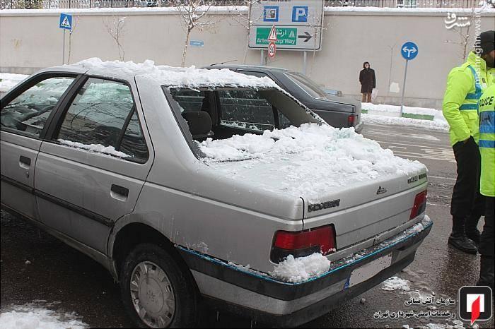 خسارت سقوط برف به خودرویی که زیر آن پارک شده بود.
