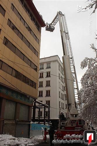 ماموران آتش نشانی در حال برف روبی سقف ساختمان هستند.