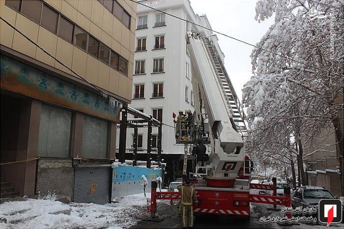 تلاش ماموران آتش نشانی برای برف روبی سقف ساختمان
