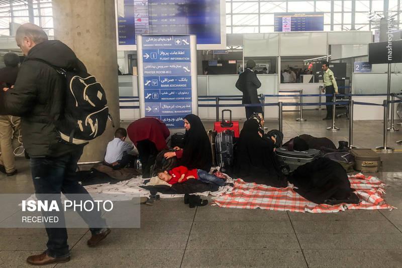 مسافران که به علت نبود مکان مناسب در کف فرودگاه خوابیده اند.