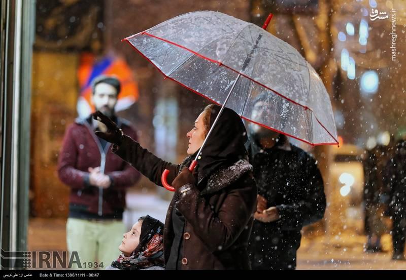 مادر و دختر زیر چتر در هوای برفی