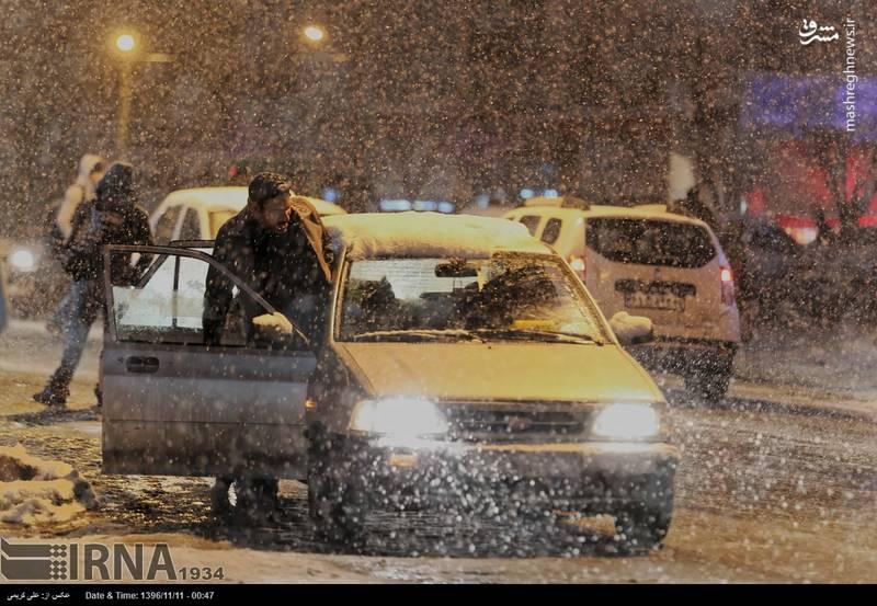 مسافرانی که زیر برف به دنبال تاکسی هستند.