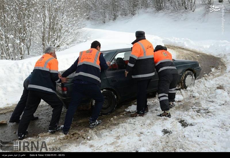 تلاش ماموران راهداری برای نجات خودروی گرفتارشده در برف
