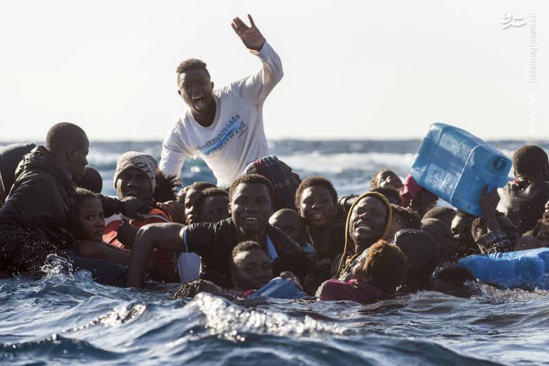 تلاش مهاجران در یک قایقِ در حال غرق در مدیترانه برای دریافت کمک