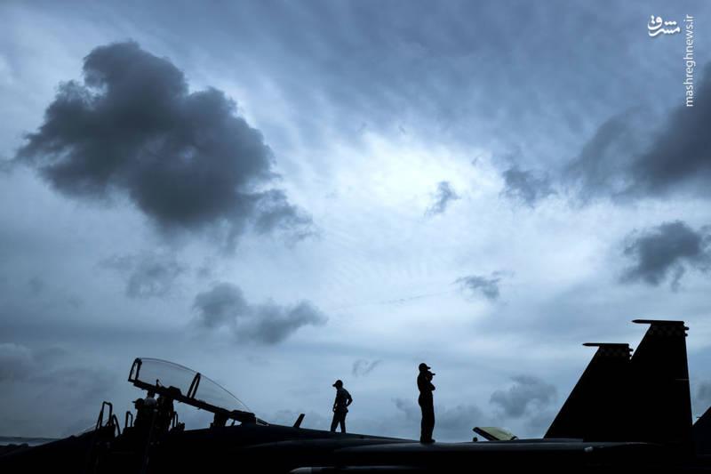 خلبانان سنگاپوری روی یک فروند جنگنده (F-15SG) ایستاده اند.