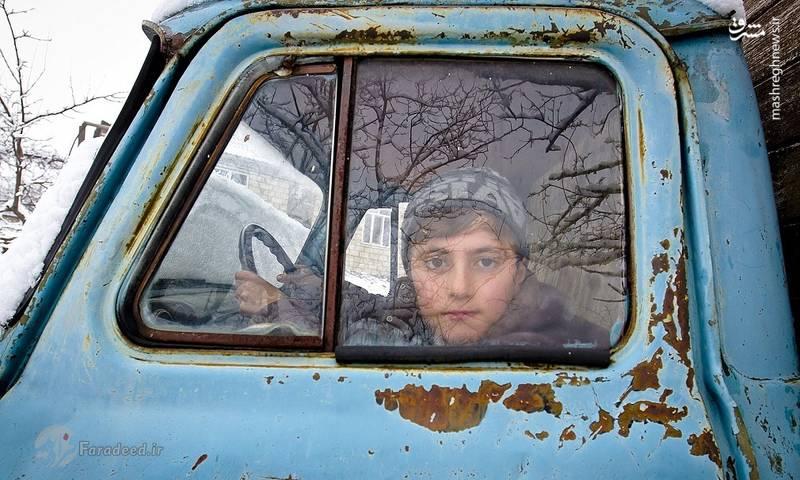 کودک روستایی که فضای گرم داخل ماشین را به سرمای قره باغ ترجیح می دهد. بسیاری از ساکنان به اختلالات روانی کودکان اشاره می کنند.