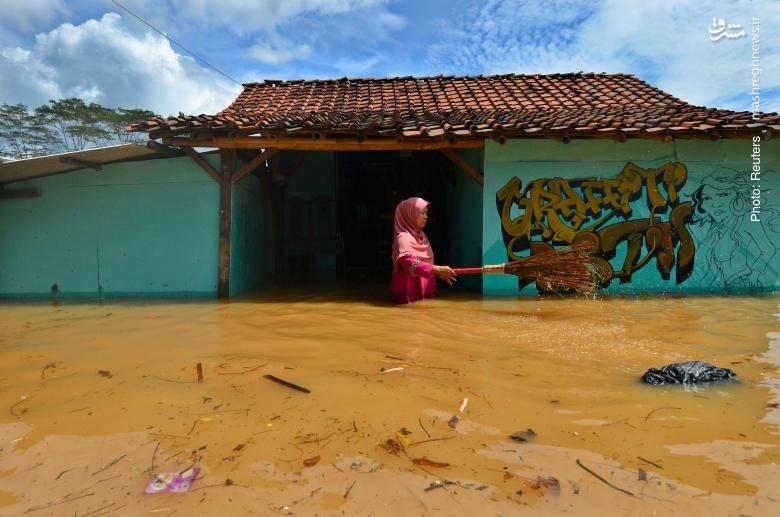 سیل در تاسیکمالای اندونزی خانمی که در حال دورکردن زبالهها از منزل خود است.