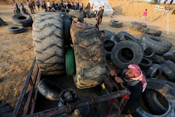 فلسطینیان در حال جمعآوری دهها حلقه لاستیک در نوار مرزی باریکه غزه به منظور آتش زدن آن در تظاهرات بازگشت