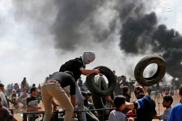 جوانان فلسطینی در حال انتقال صدها حلقه لاستیک به نوار مرزی باریکه غزه به منظور آتش زدن آن و ایجاد دود غلیظ جهت در امان ماندن از گلولههای نظامیان اشغالگر صهیونیست
