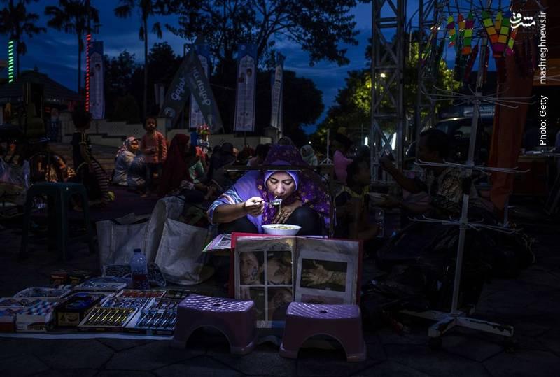 تصویری دلنشین از افطار یک فروشنده در سورابایای اندونزی