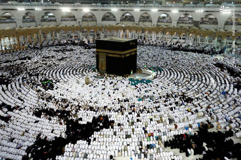 نماز جماعت دور خانه خدا پس از یک افطار مختصر که خادمان مسجد با سرعت و نظم میان صفوف توزیع میکنند.