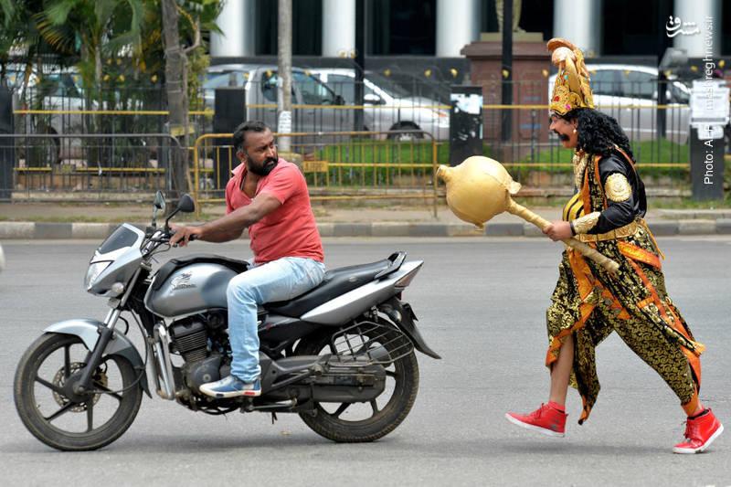 مشارکت یک هندی در لباس یکی از خدایان هندو در پویش «هفته سلامتی جادهها». احتمالاً وی در حال تذکر به موتورسوار برای استفاده از کلاه ایمنی است.