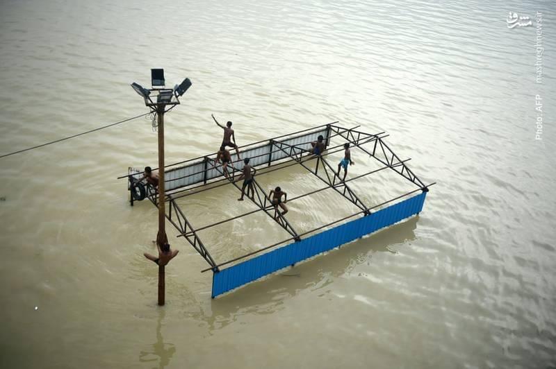 بازی بر اسکلت سقف یک خانه متروکه پس از طغیان رودخانه گَنگ و سیل در اللهآباد هند