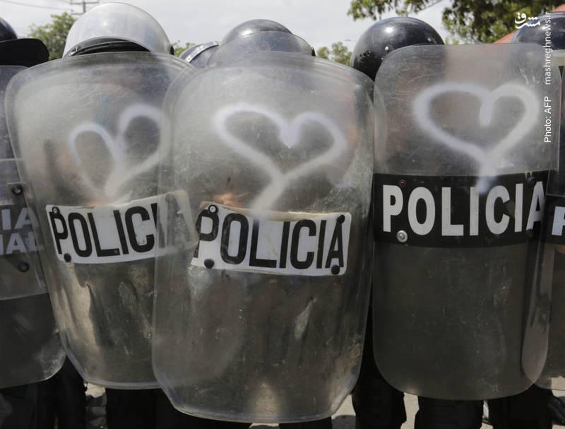 ترسیم نشان محبت بر تجهیزات پلیس ضدشورش طی تظاهرات علیه رئیسجمهور نیکاراگوا
