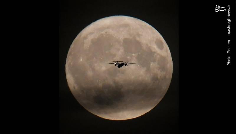 تصویر هواپیمای مسافری روبروی ماه کامل در لندن