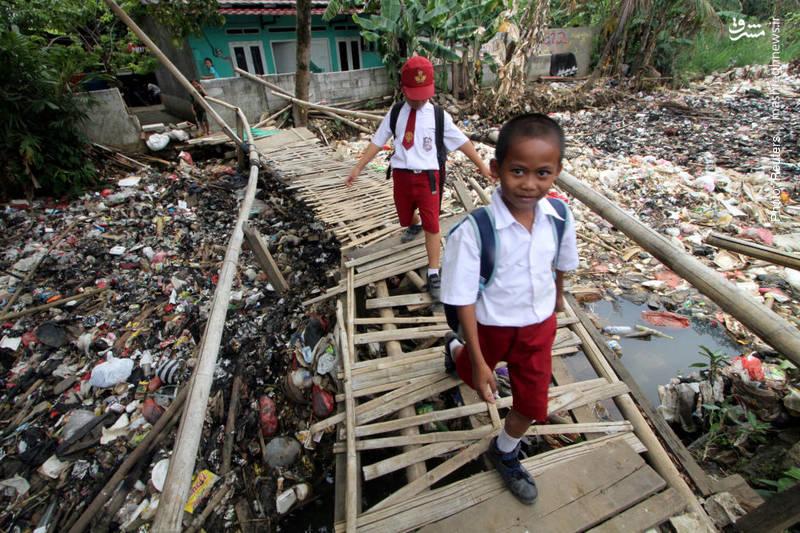 عبور دانشآموزان در یکی از شهرهای اندونزی از روی رودخانهای پر از زباله