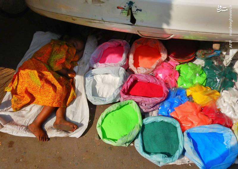 دستفروش هندی، مشغول استراحت کنار بساط پودر رنگ