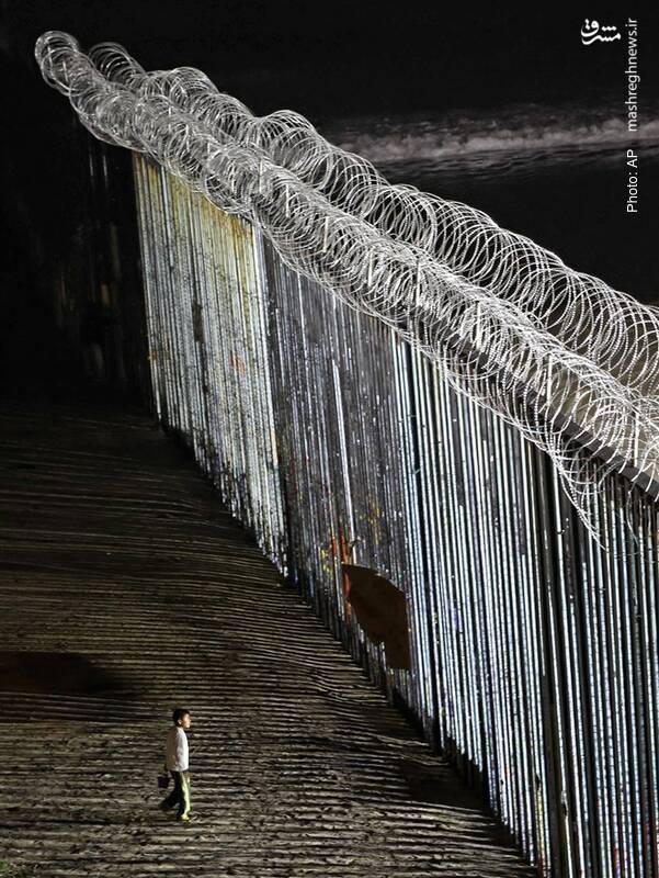 پسری در کنار دیوار مرزی مکزیک و آمریکا در تیخوانا