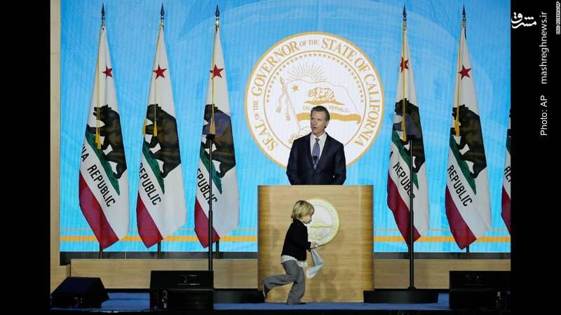 سخنرانی فرماندار کالیفرنیا در مراسم آغاز بکار وی در حالی که فرزندش آزادانه روی سن میدود.