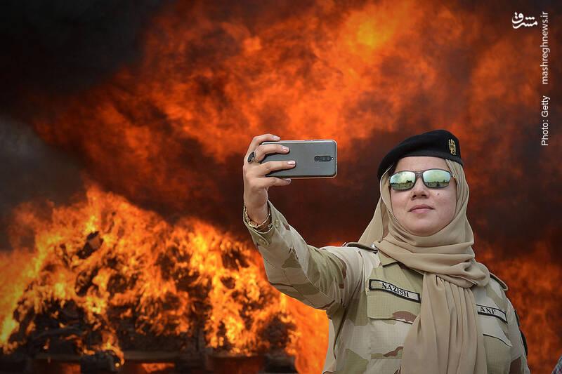 سلفی سرباز پاکستانی در کنار مواد مخدری که کشف و به آتش کشیده شده است.