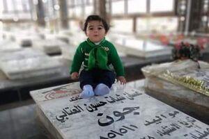 عکس/ کودکی که سر مزار پدرش رفت