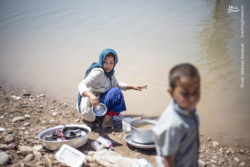 زنان روستا ظرفهای خود را در آب سیلاب میشویند.