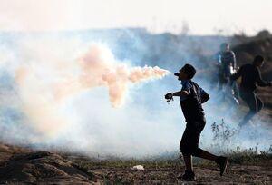 عکس/ حرکت جالب جوان فلسطینی با گاز اشکآور