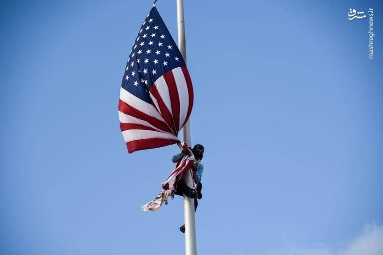 یک معترض پرچم آمریکا را از ساختمان ایالتی در شهر سانخوآن پورتوریکو آمریکا پایین میکشد