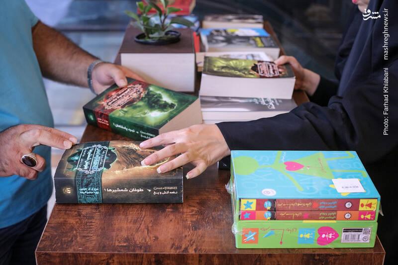 کتاب های قطور مجموعه «نغمه های آتش و یخ» نظر جفتمان را جلب می کند. با خود فکر می کنم چه نوجوانانی پای این کتاب های قطور می نشینند و آیا همه محتوای آن ها برای این سنین مناسب است؟