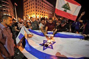 عکس/ آتش زدن پرچم اسرائیل توسط معترضان لبنان