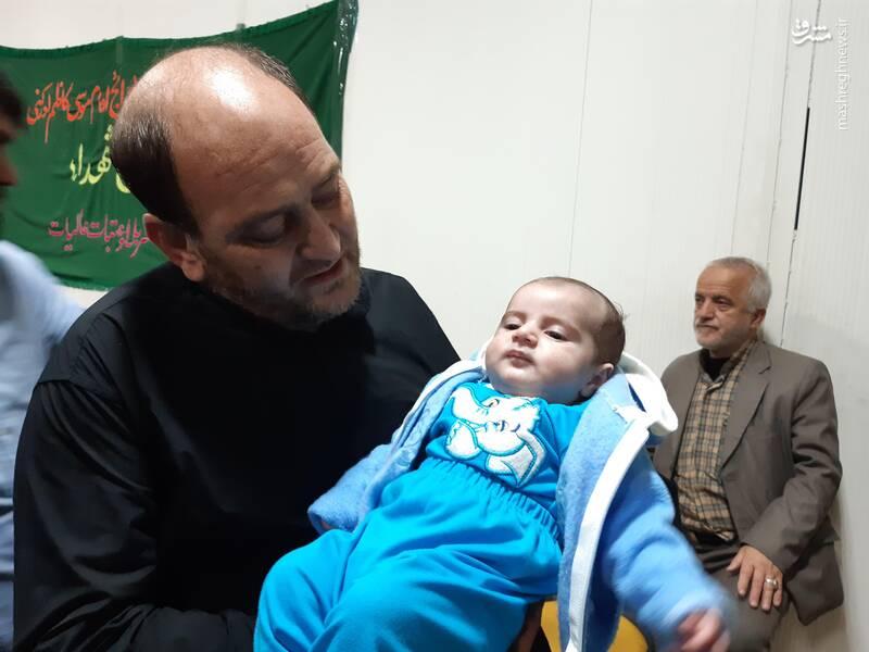 نوزاد شهید مرتضی ابراهیمی در آغوش پدر شهید مدافع حرم، عباس آبیاری